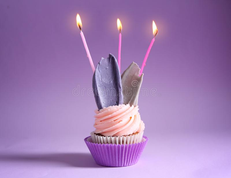 Delicious birthday cupcake with burning candles on color background royalty free stock photos