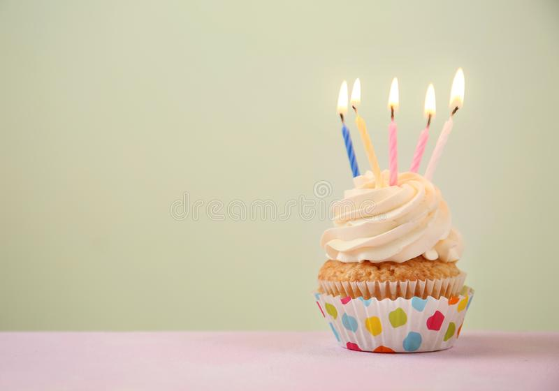 Delicious birthday cupcake with burning candles on color table stock images