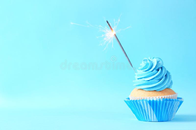 Delicious birthday cupcake with sparkler on color background stock image