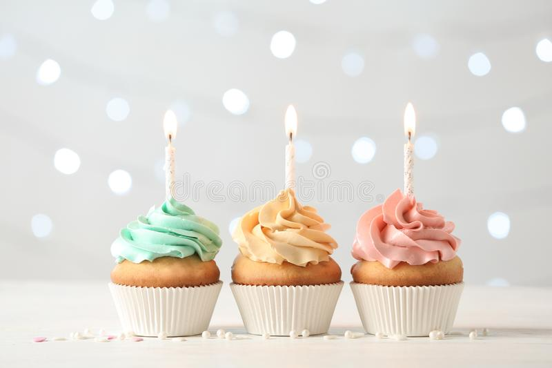 Delicious birthday cupcakes with burning candles royalty free stock photo