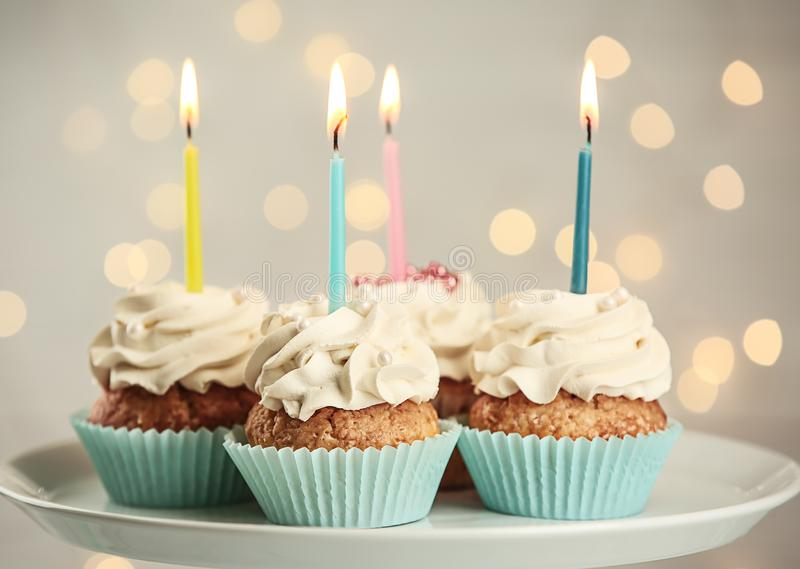 Delicious birthday cupcakes with burning candles on plate stock photo