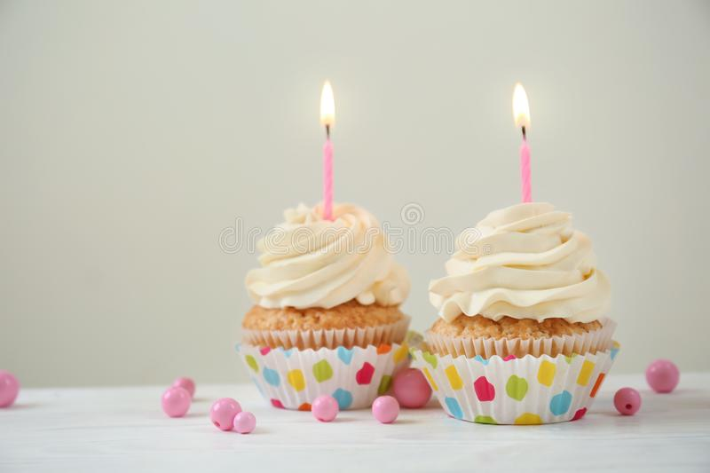 Delicious birthday cupcakes with burning candles on white wooden table stock image
