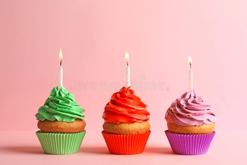 Delicious birthday cupcakes with candles. On color background stock photos