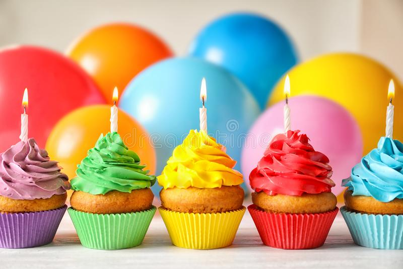 Delicious birthday cupcakes with candles. And blurred balloons on background stock photo