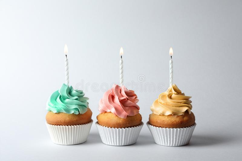 Delicious birthday cupcakes with candles. On gray background stock photo