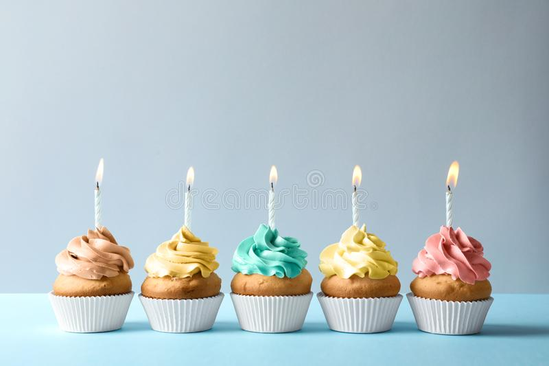 Delicious birthday cupcakes with candles on light background stock image