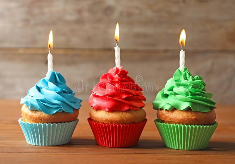 Delicious birthday cupcakes with candles. On table stock photos