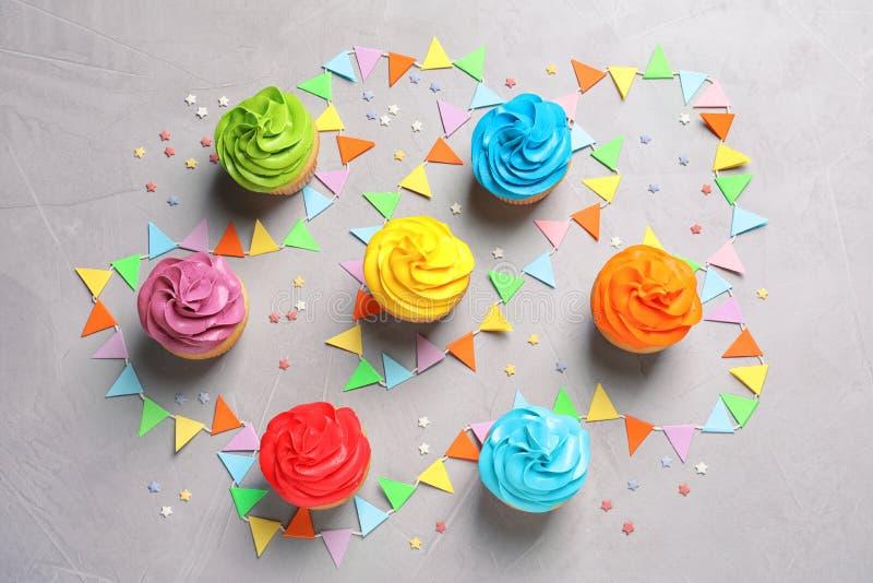 Delicious birthday cupcakes. On gray background stock photos