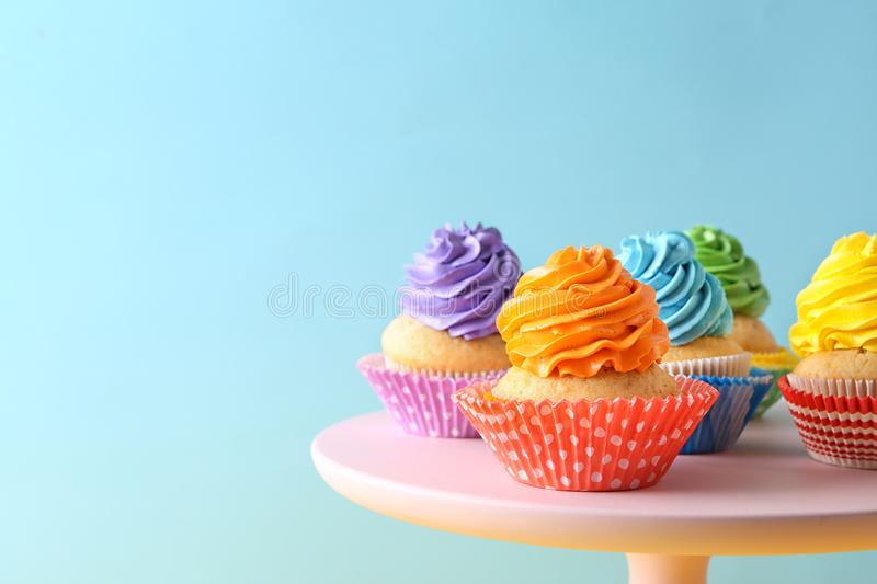 Delicious birthday cupcakes on stand against color background royalty free stock photo