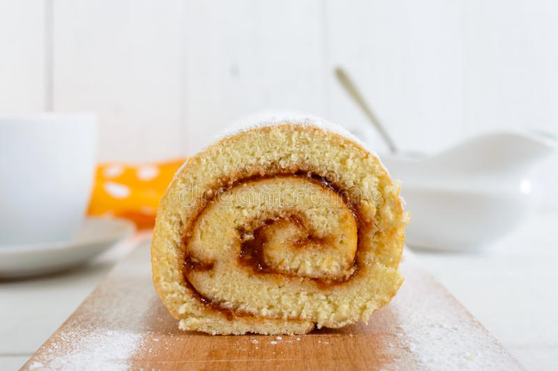 Delicious biscuit roll with apricot jam on a white wooden table. Cutting close-up. royalty free stock images