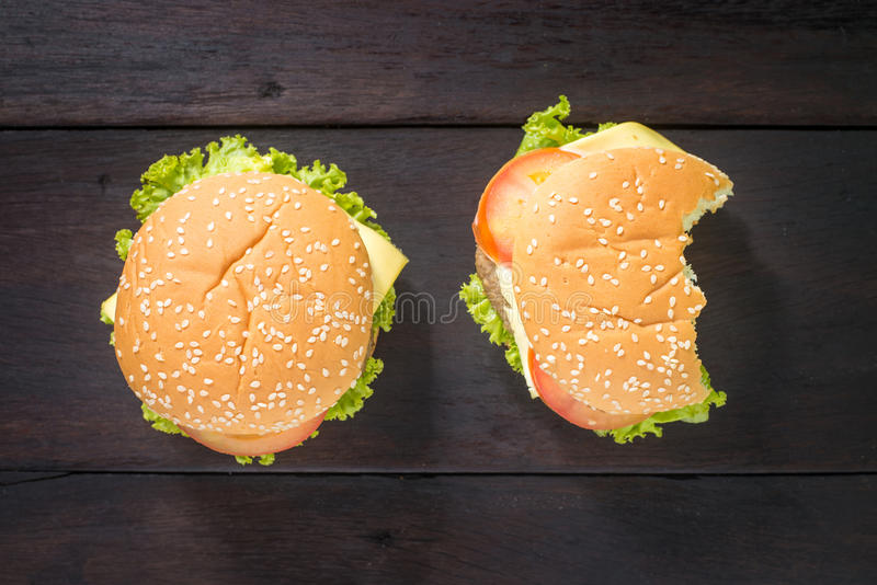 Delicious bitten hamburger on wooden background, shot from upper view. Fast food with delicious bitten hamburger, shot from upper view royalty free stock images
