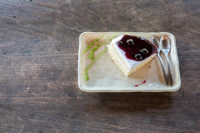 Delicious blueberry cheesecake. Blue berry cake slices on wood plate. stock image