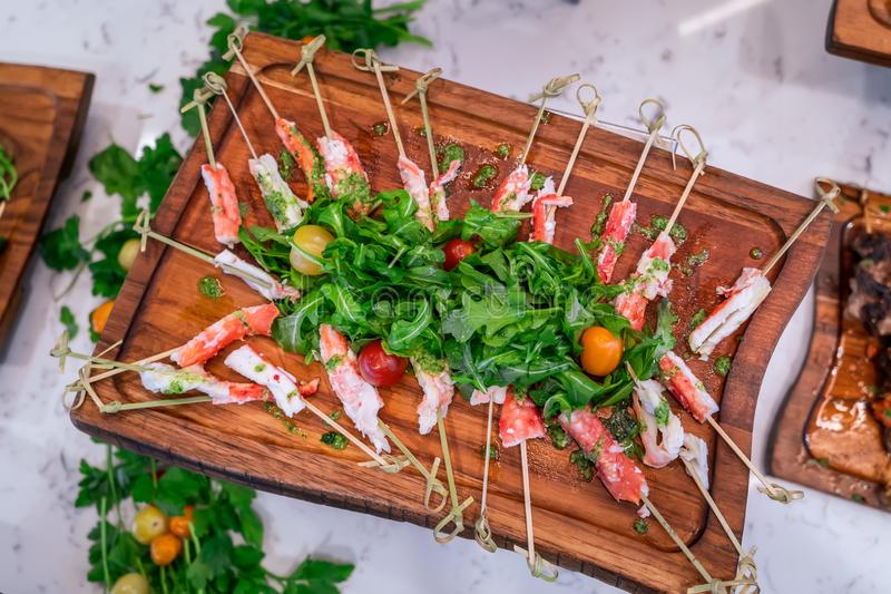 Delicious board of crab leg skewers and arugula salad. stock photos