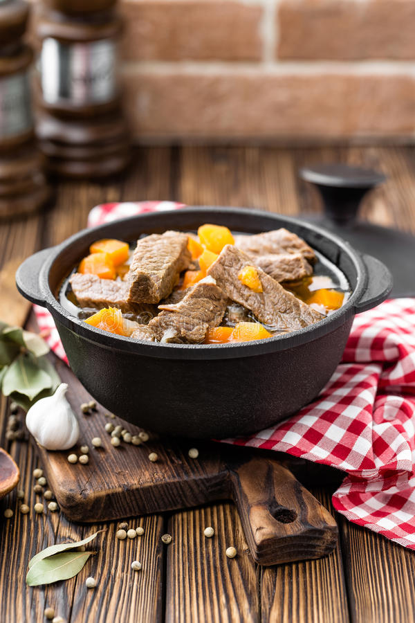 Delicious braised beef meat in broth with vegetables, goulash. On wooden table royalty free stock photography