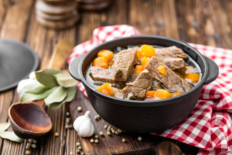 Delicious braised beef meat in broth with vegetables, goulash. On wooden table stock image