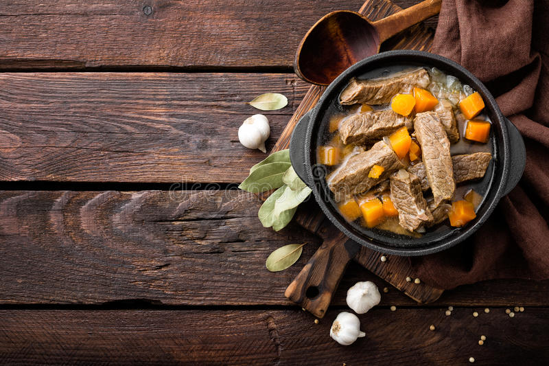 Delicious braised beef meat in broth with vegetables, goulash. On wooden table royalty free stock photos