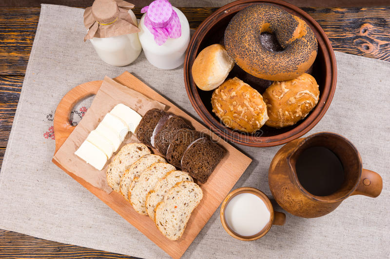 Delicious bread and cheese pub lunch. With sliced whole grain bread and a bowl of assorted rolls served with bottles of fresh farm milk, overhead view stock photography