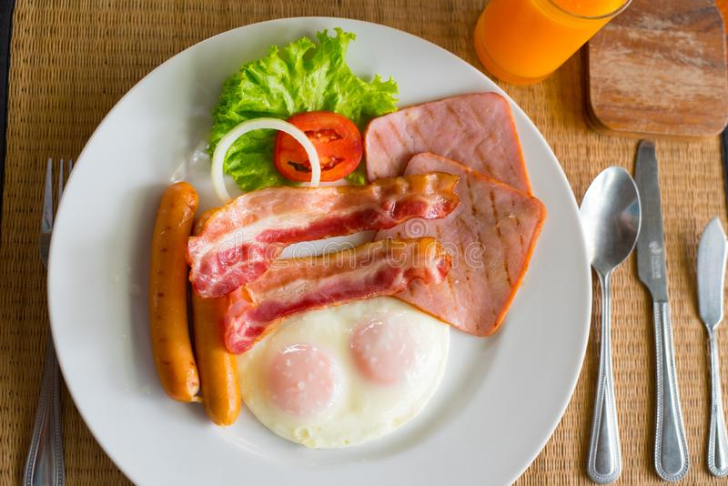 Delicious breakfast with bacon ham sausage and eggs. stock photo
