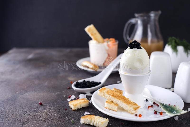 Delicious breakfast with boiled eggs and crispy toasts. On a dark stone background, copy space royalty free stock image