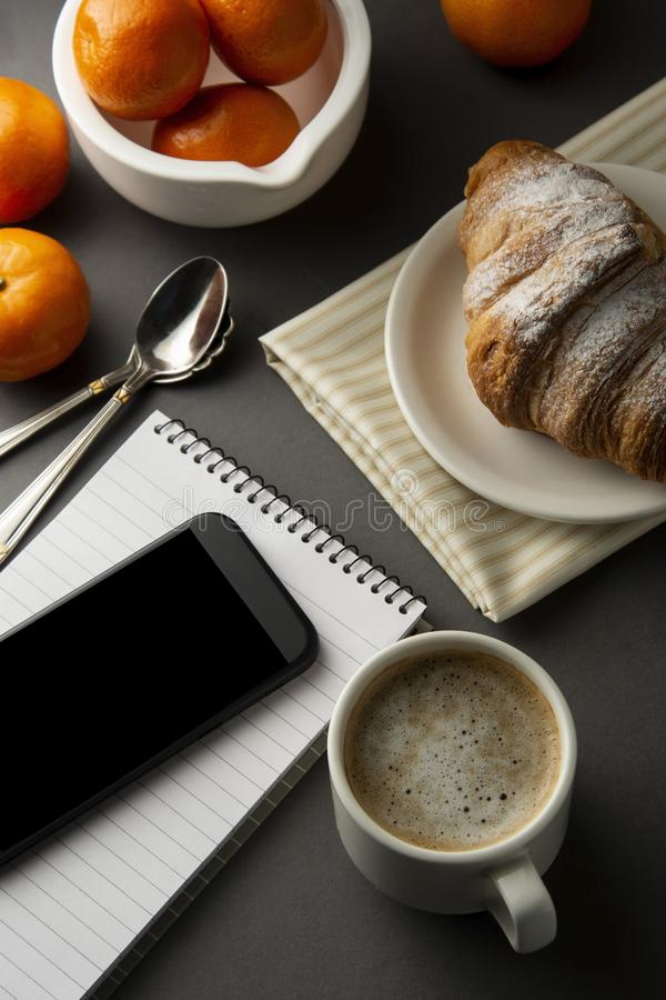 Delicious breakfast coffee with croissant and citrus fruits. Heart shaped box. Work table with smart phone. French pastry and cup. Delicious breakfast coffee royalty free stock images