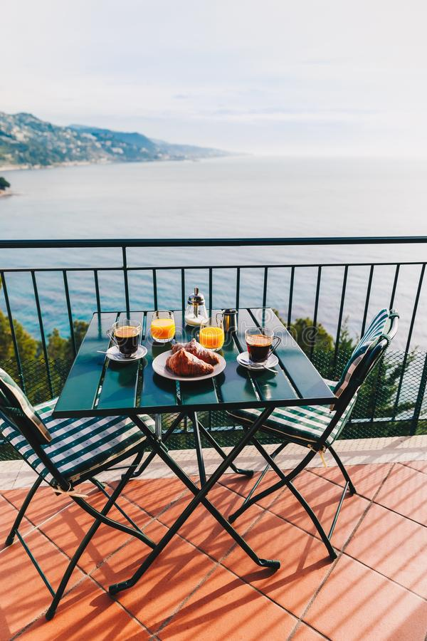 Delicious breakfast with coffee, pastry, and orange juice served on the balcony with sea view royalty free stock photography