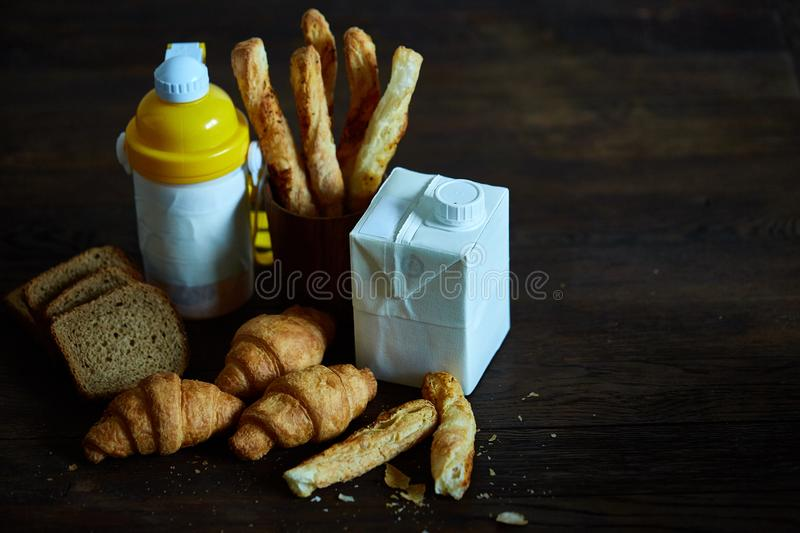 Delicious breakfast concept with fresh pastry, milk and bottle of beverage over rustic wooden background, top view, royalty free stock images