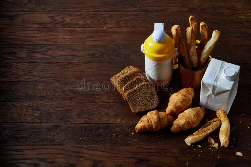 Delicious breakfast concept with fresh pastry, milk and bottle of beverage over rustic wooden background, top view, stock images