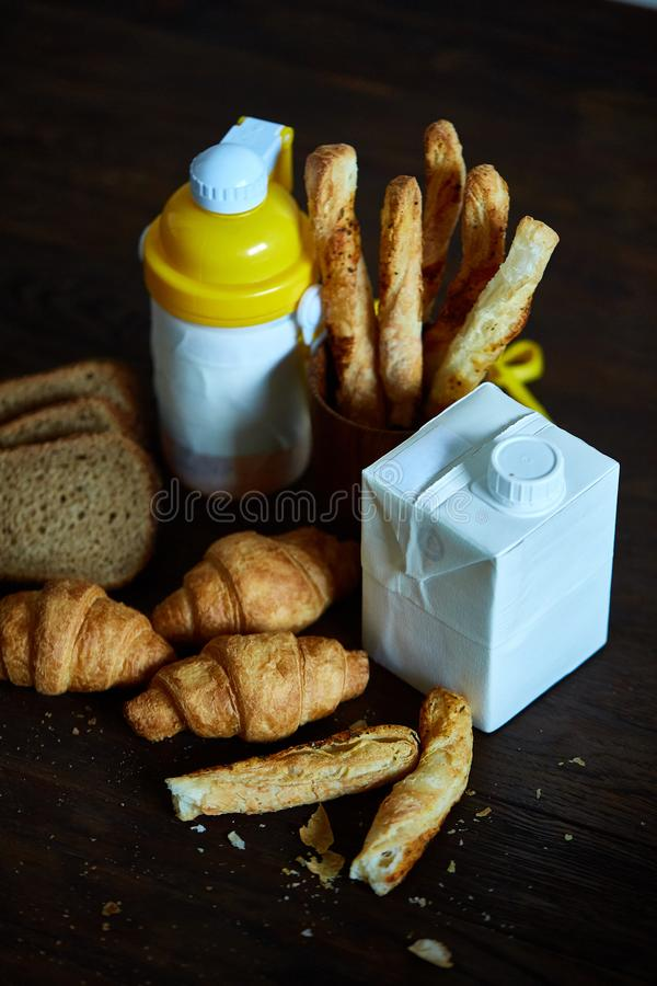 Delicious breakfast concept with fresh pastry, milk and bottle of beverage over rustic wooden background, top view, stock image