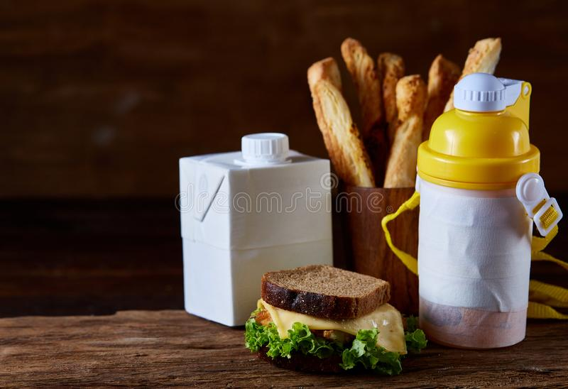 Delicious breakfast concept with fresh pastry, milk and bottle of beverage over rustic wooden background, top view, royalty free stock photography