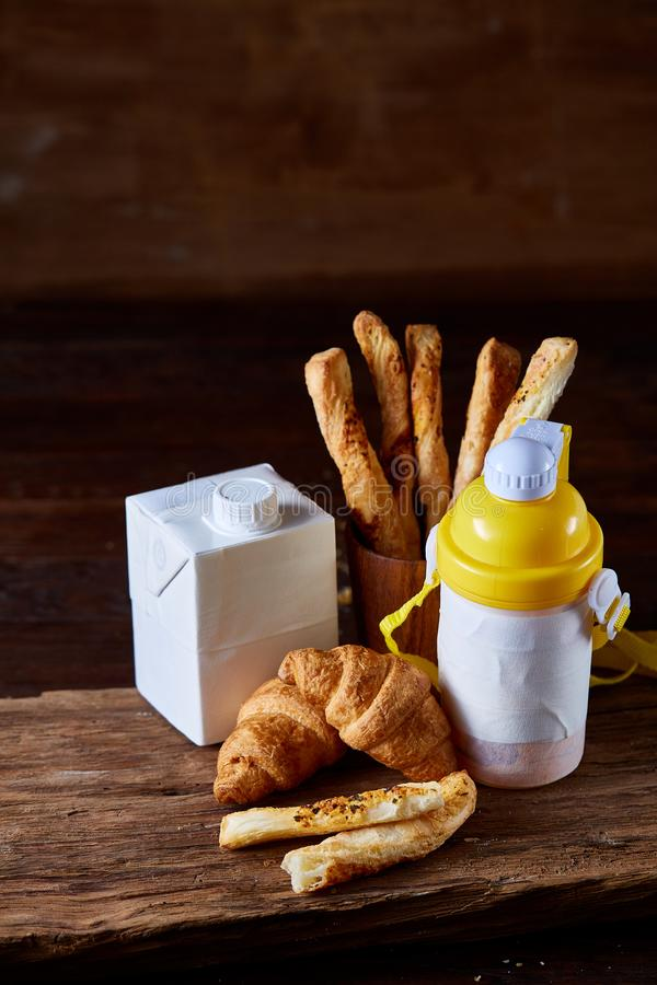 Delicious breakfast concept with fresh pastry, milk and bottle of beverage over rustic wooden background, top view, royalty free stock photo
