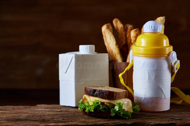 Delicious breakfast concept with fresh pastry, milk and bottle of beverage over rustic wooden background, top view, stock photography