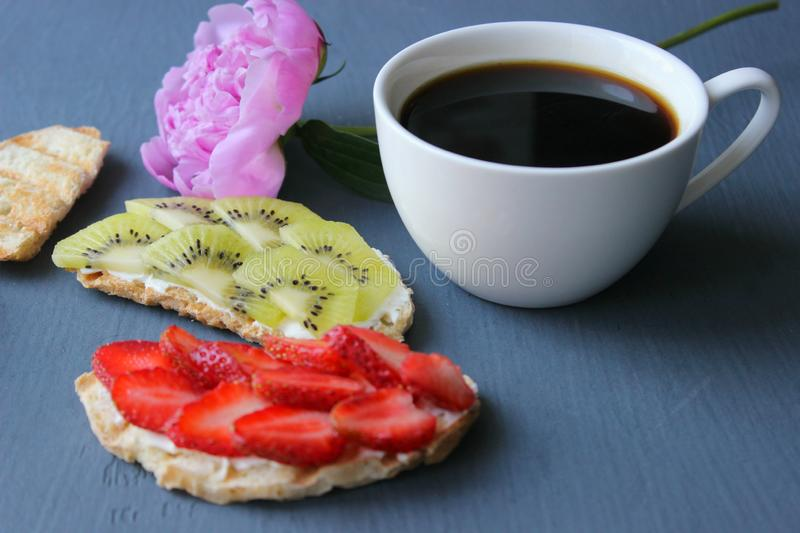 Delicious breakfast. A Cup of coffee and Bruschetta with cottage cheese and fresh strawberries and kiwi berries on toasted whole g. Rain bread. French toast with stock image