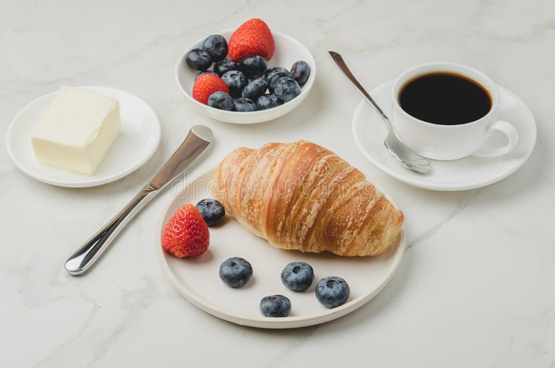 Delicious breakfast with fresh coffee, fresh croissants and berries. Selective focus stock photography