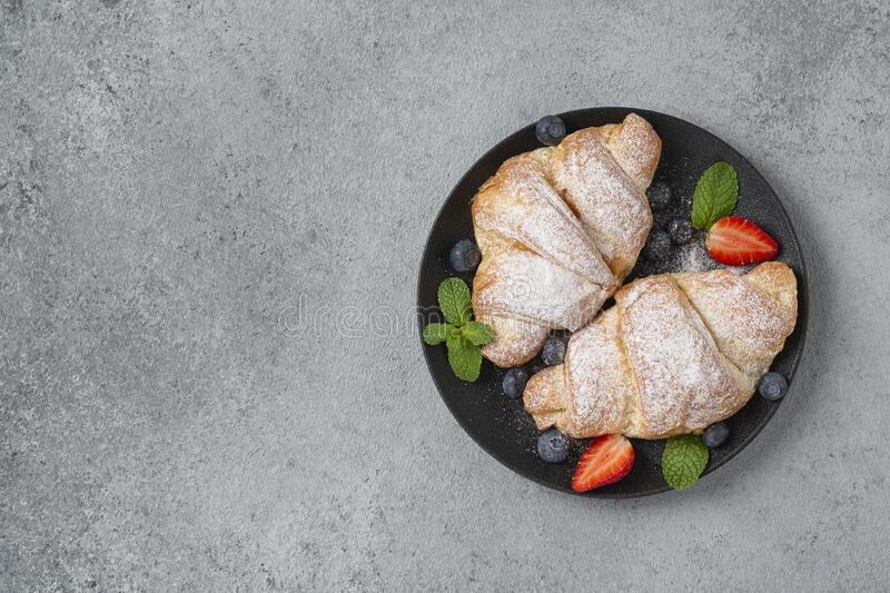 Delicious breakfast with fresh croissants and fresh ripe berries. Freshly baked croissants with strawberries and blueberries. stock image