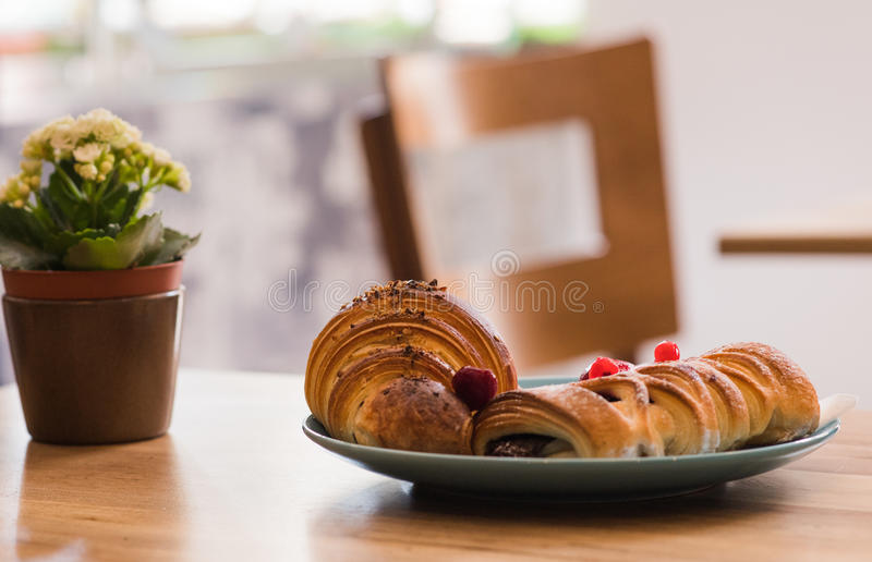 Delicious breakfast with fresh puff pastry roll filled with fruit sauce and croissant with chocolate cream on wooden table stock image