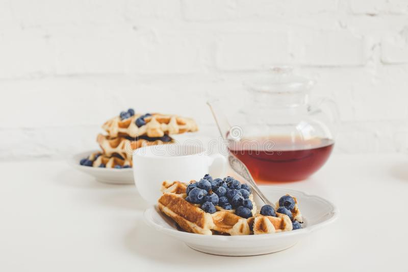 Breakfast of freshly baked waffles with blueberries and tea royalty free stock photos