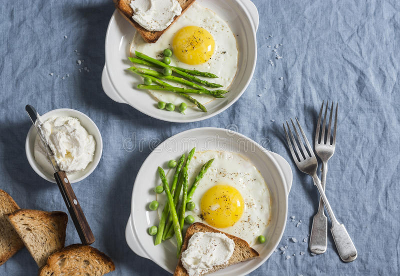 Delicious breakfast - fried egg, asparagus and cheese sandwich. On a blue background royalty free stock photo