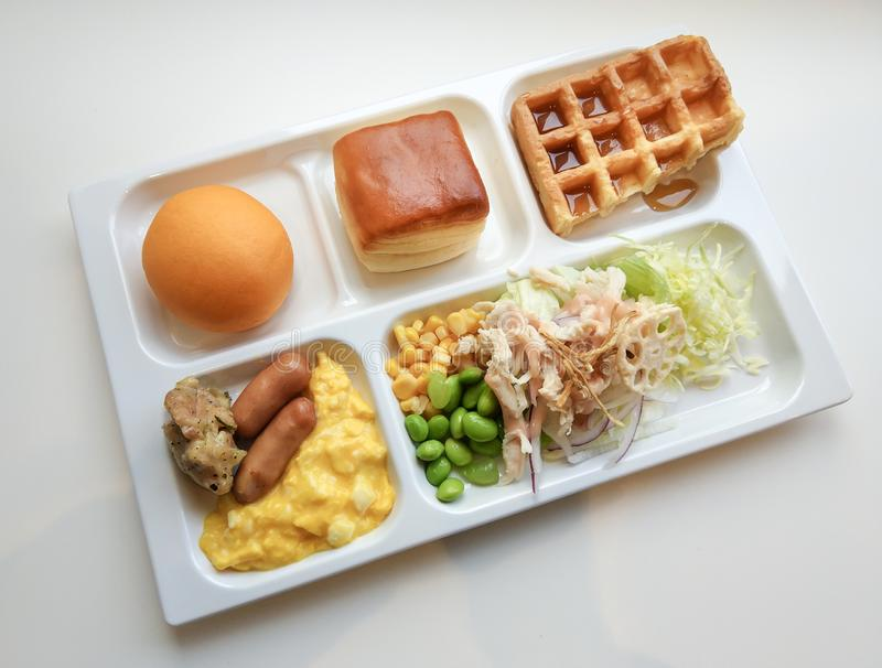 Delicious breakfast good morning 0n white tray. Delicious breakfast good morning with bread, bun, waffle, scrambled eggs, sausage and salad vegetables. Tray of royalty free stock image