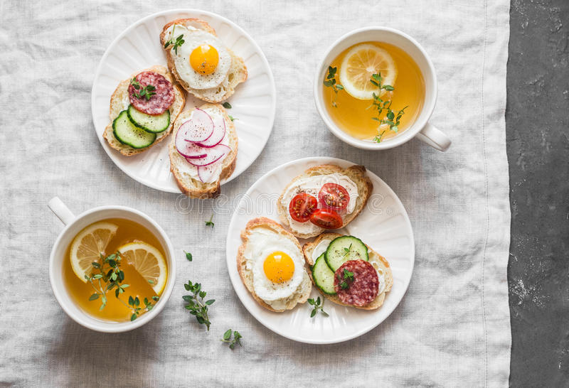 Delicious Breakfast - mini sandwiches with cream cheese, vegetables, quail eggs, salami and green tea with lemon and thyme. Sandwi royalty free stock photo