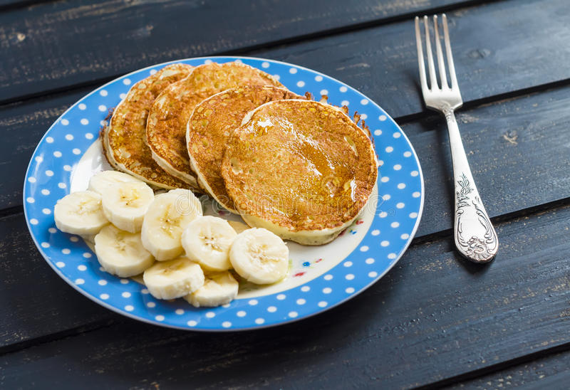 Delicious Breakfast pancake with honey and banana slices. On dark wooden surface royalty free stock photography