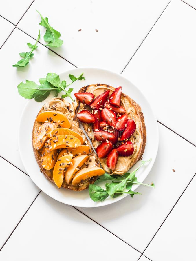 Delicious breakfast or snack - peanut butter strawberries, apricots and flaxseed sandwiches on a light background, top view stock photography
