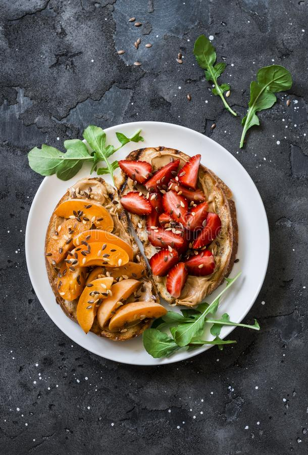 Delicious breakfast or snack - peanut butter strawberries, apricots sandwiches on a dark background, top view stock images