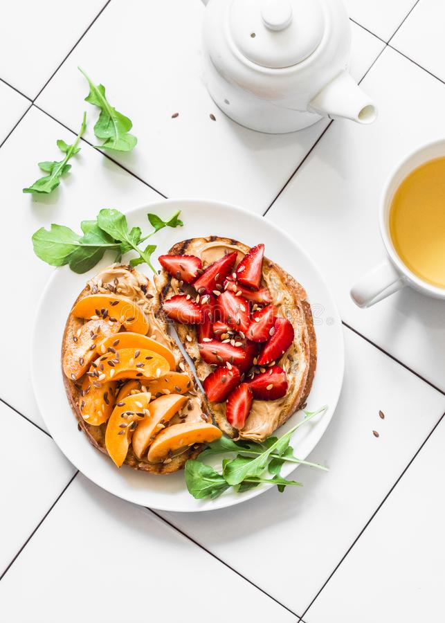 Delicious breakfast or snack - peanut butter strawberries, apricots sandwiches and green tea on a light background, top view royalty free stock photography