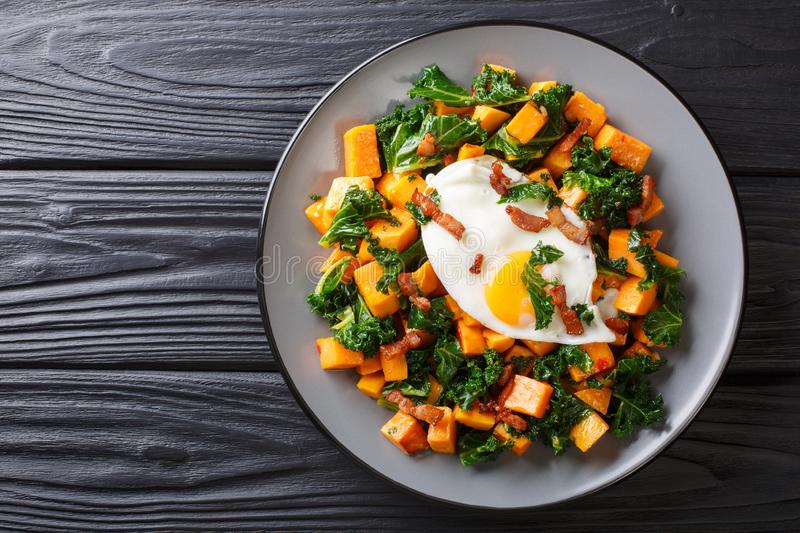Delicious breakfast of sweet potato with kale, bacon and fried egg close-up on a plate. horizontal top view. Delicious breakfast of sweet potato with kale, bacon royalty free stock image