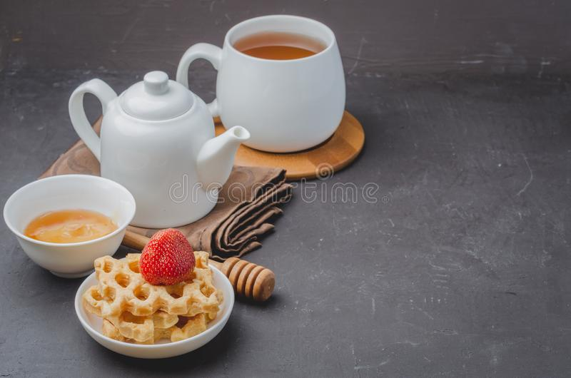 Delicious breakfast with tea, honey and wafers decorated with fresh strawberry on a stone table. Copyspace stock photos