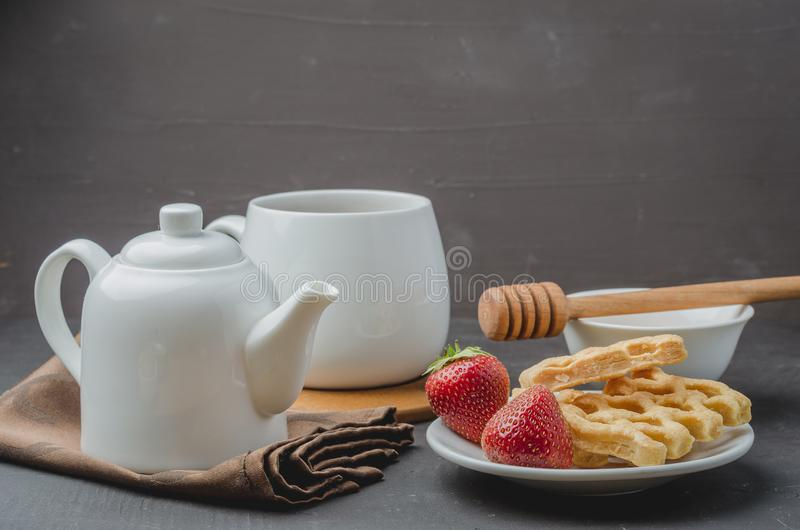 Delicious breakfast with tea, honey and wafers decorated with fresh strawberry on a stone table. Selective focus stock images