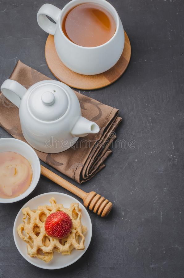 Delicious breakfast with tea, honey and wafers decorated with fresh strawberry on a stone table. Top view stock image