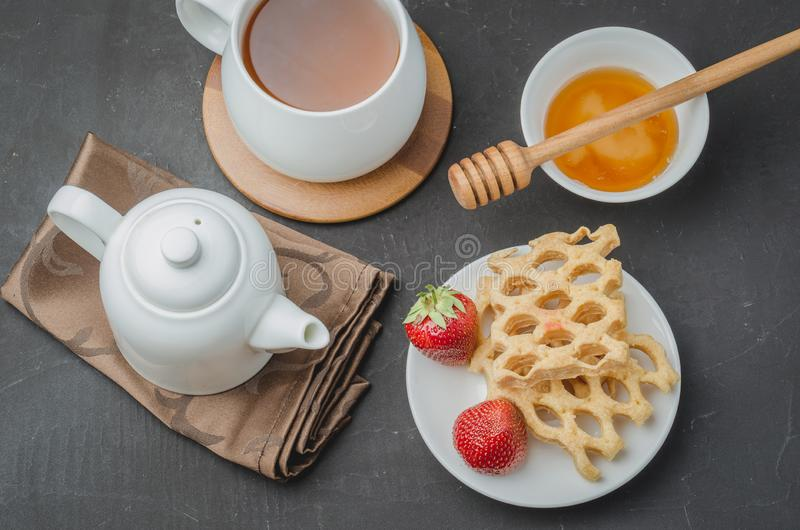 Delicious breakfast with tea, honey and wafers decorated with fresh strawberry on a stone table. Top view stock photos