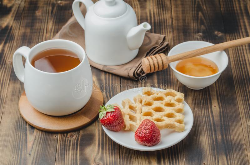 Delicious breakfast with tea, honey and wafers decorated with fresh strawberry on a wwoden table royalty free stock images