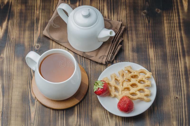 Delicious breakfast with tea, wafers decorated with fresh strawberry, top view royalty free stock images